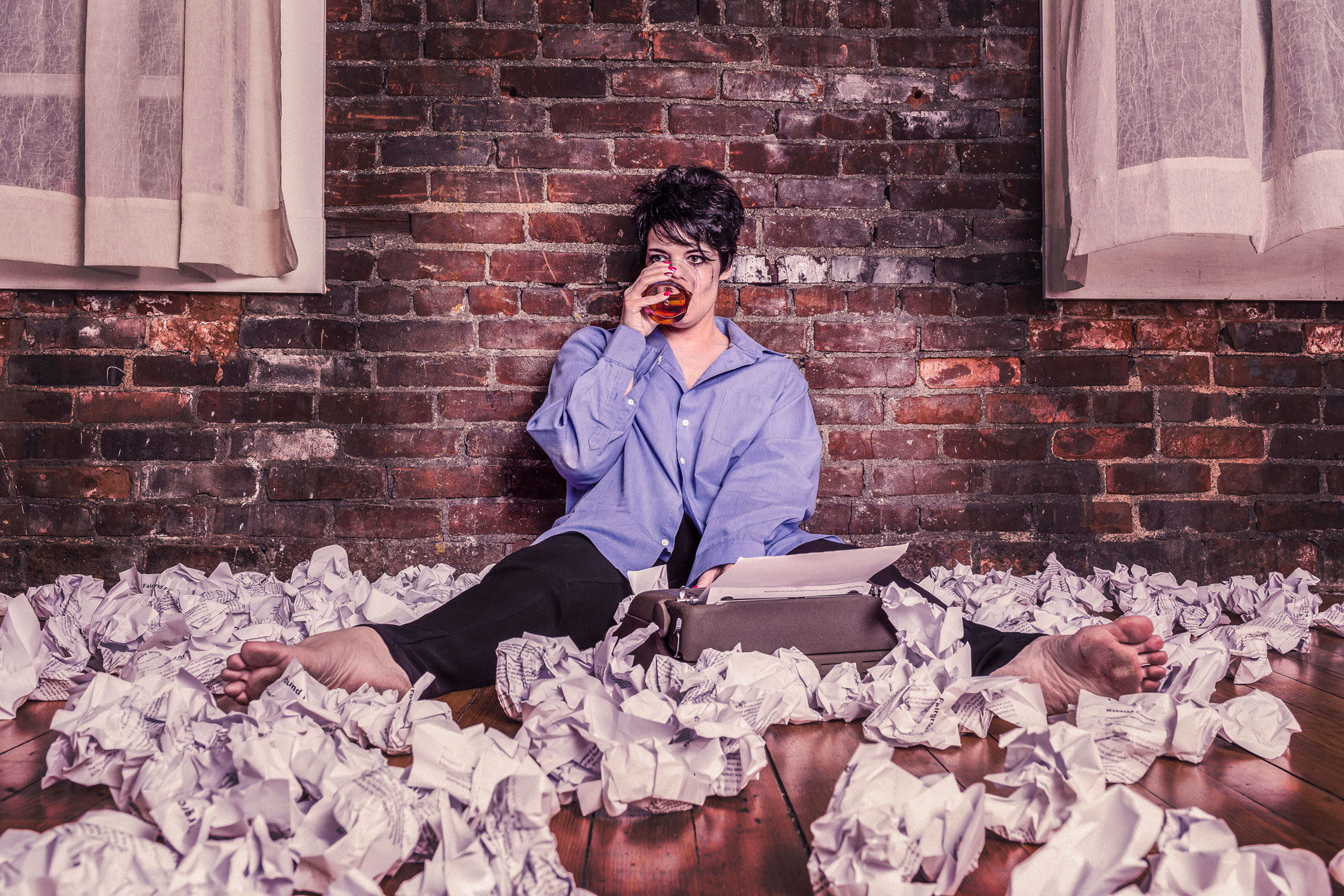 journalist sitting on floor surrounded by paper wads