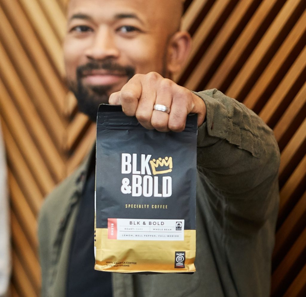 Pernell Cezar, Founder of Blk & Bold coffee holds coffee bag.