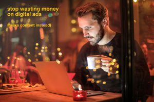 "man looking at laptop with coffee. type says ""stop wasting money on digital ads (make content instead)"""