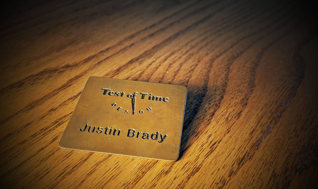 Justin Brady's Test of Time Design name badge made of bronze.
