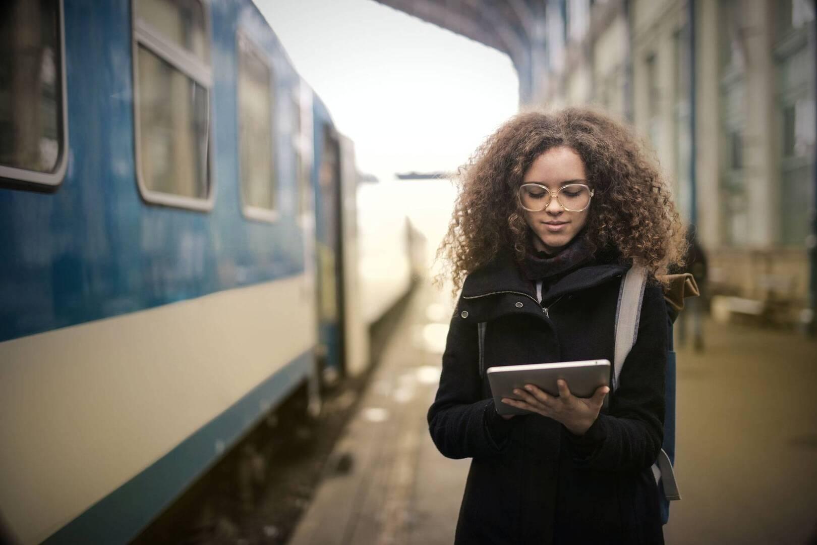 woman in black coat walking near train