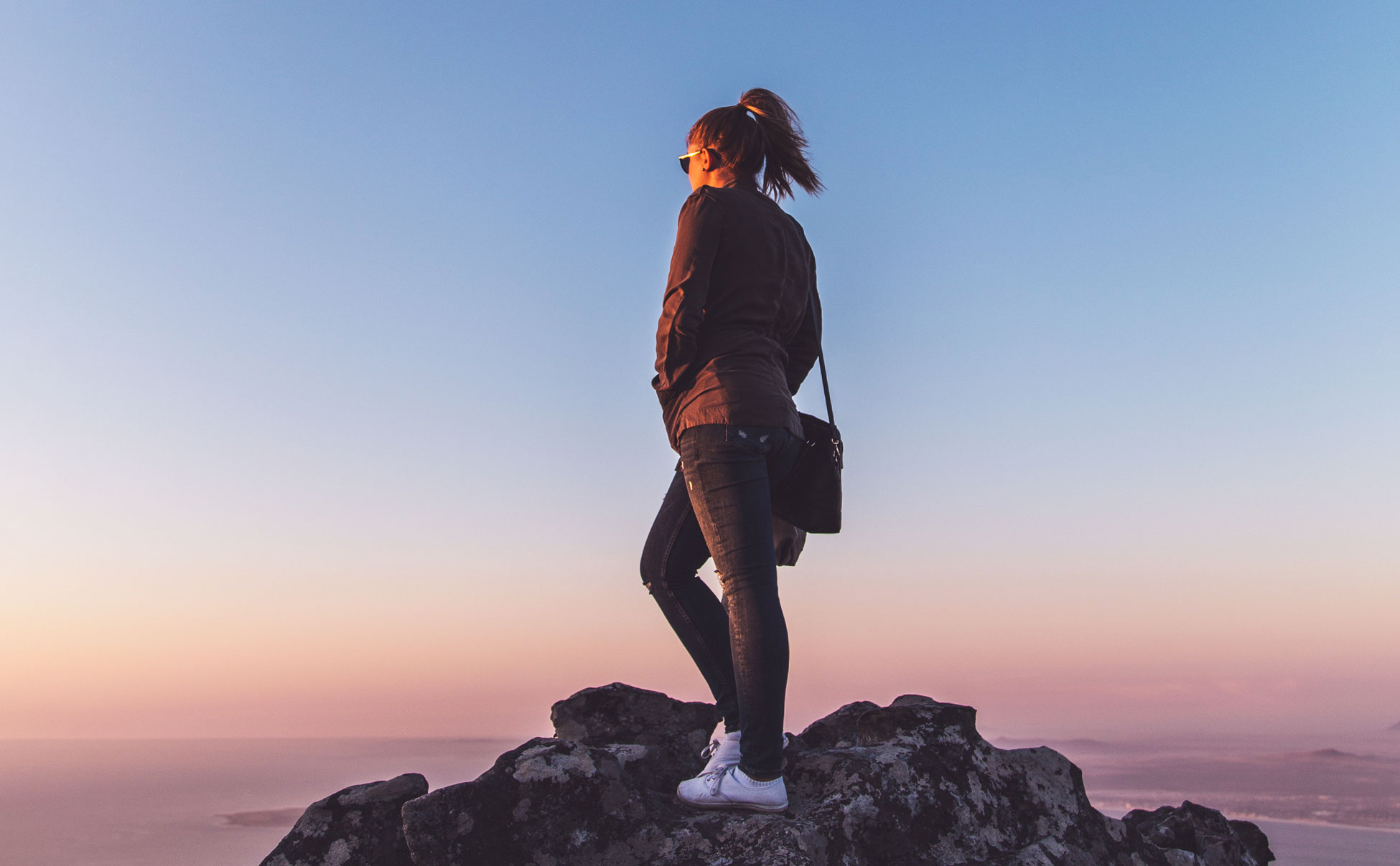 woman stands on rock