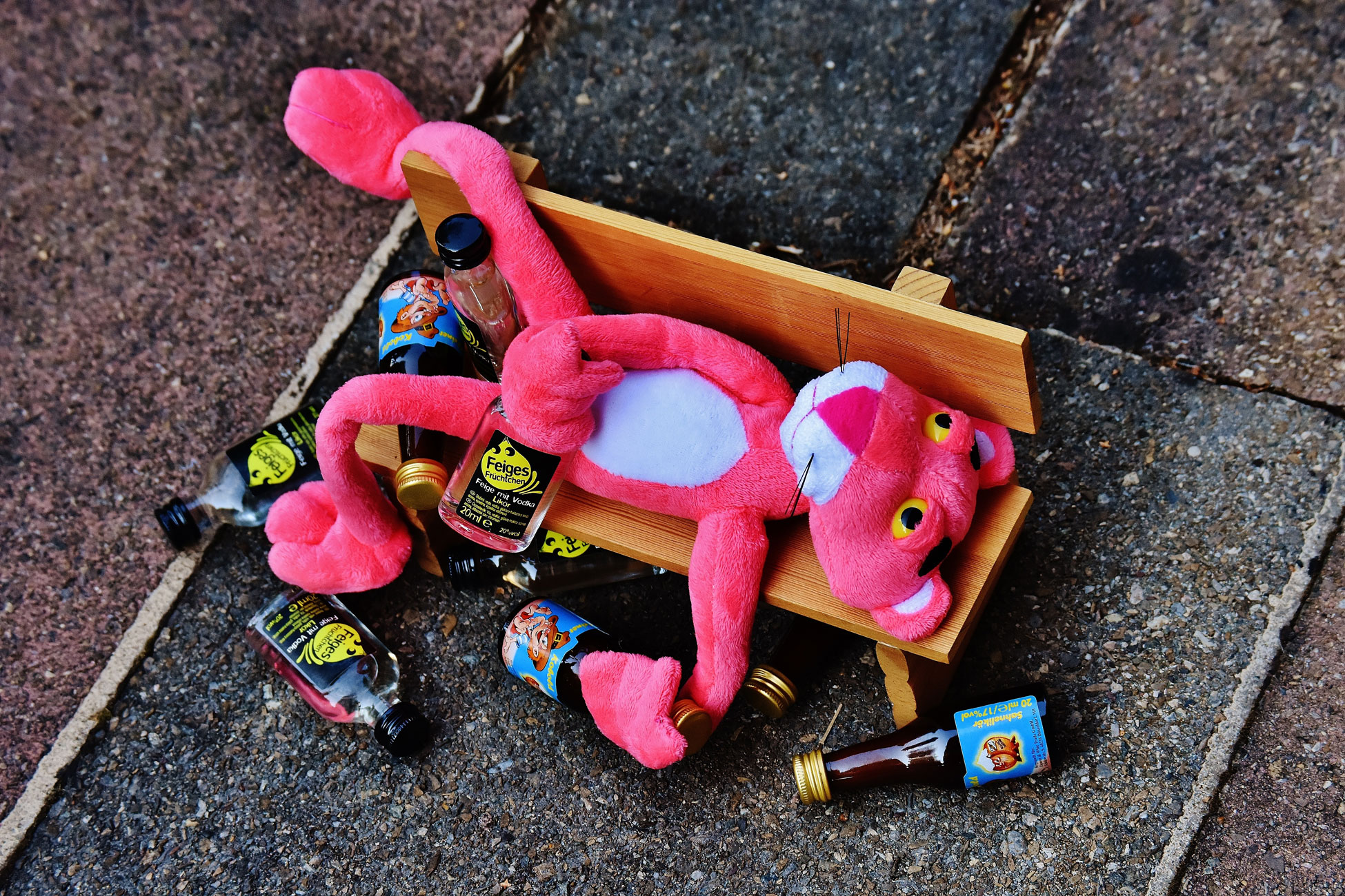 Pink panther plush toy positioned next to empty beer bottles