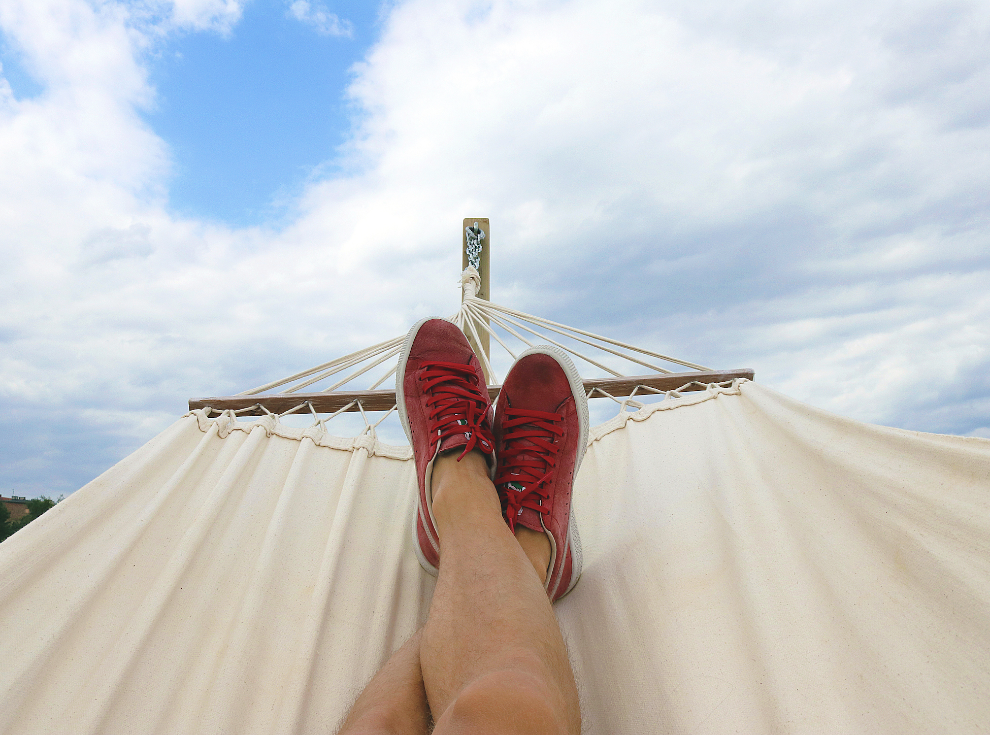 guy with red sneakers resting on hammock
