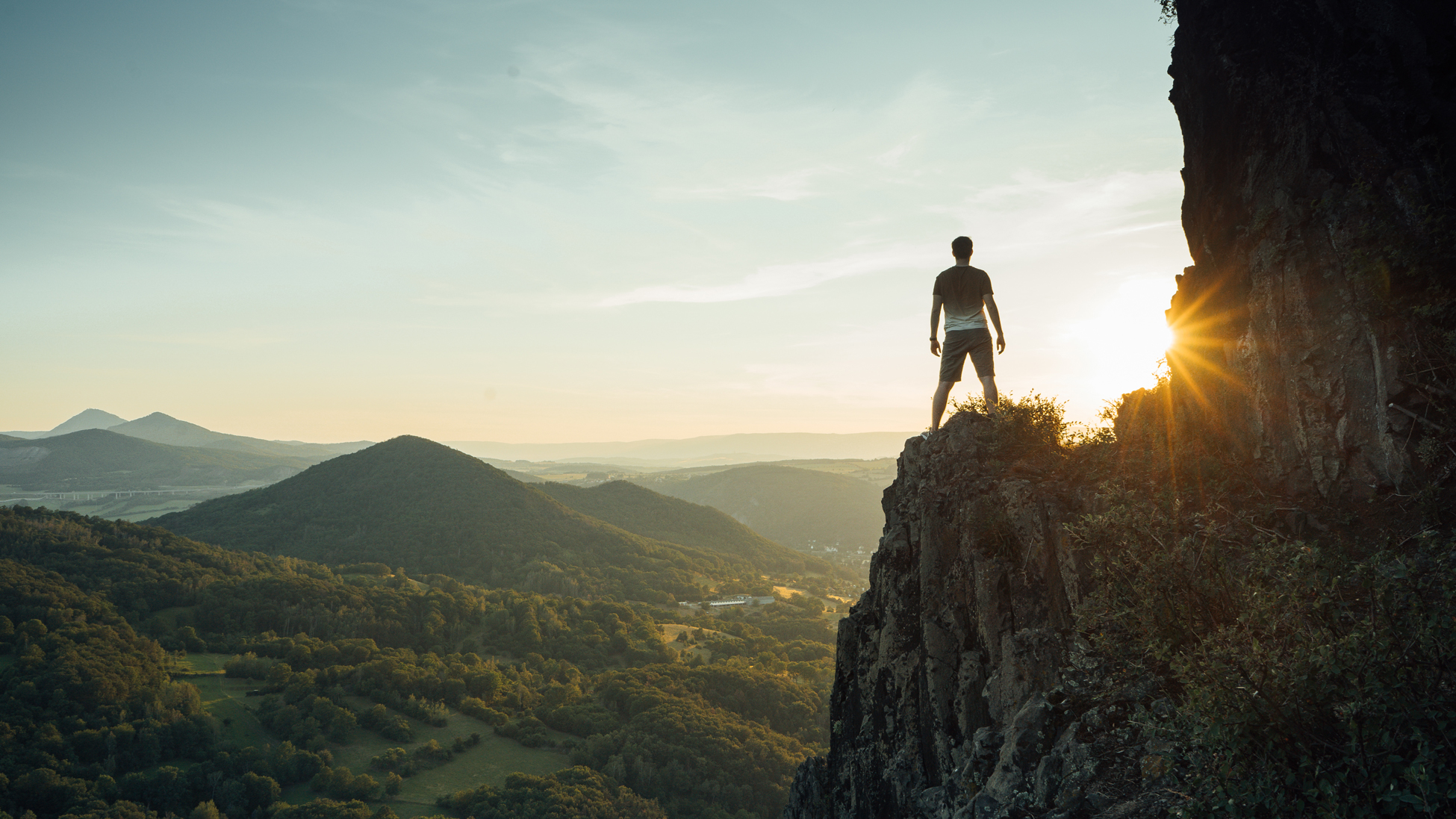 man standing on cliff overlooking valley with sun setting in background