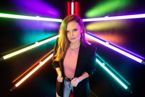 Founder of Selfie WRLD, Ashley Wilkerson stands in front of neon lights.