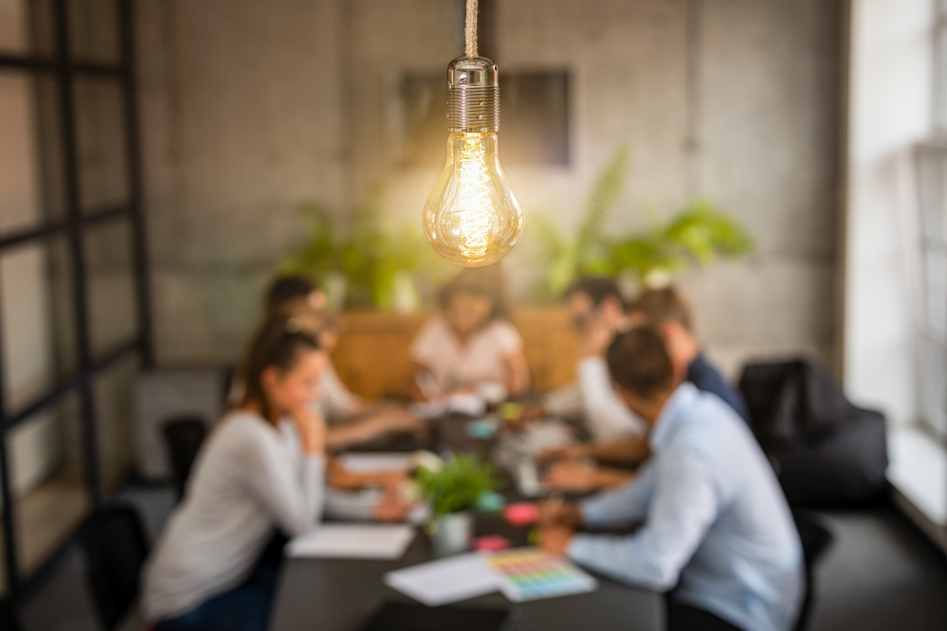 A group of people collaborating. A large lightbulb appears in the foreground.