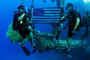 Jay Ly underwater with an American Flag