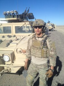 Jay Ly next to a Humvee